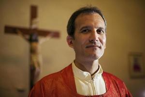 Porträt des glücklichen katholischen Priesters, der Kamera in der Kirche lächelt foto