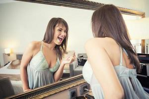 fröhliche junge Frau vor dem Spiegel, der Make-up aufträgt foto