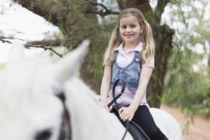 lächelndes Mädchen, das Pferd im Park reitet foto