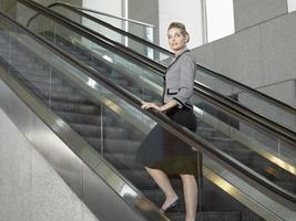 selbstbewusste Geschäftsfrau, die auf Rolltreppe steht foto
