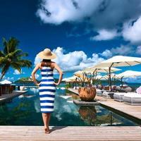 Frau Seemann im Kleid nahe am Pool gestreift foto