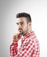 Porträt des selbstbewussten jungen bärtigen Mannes, der Kamera betrachtet