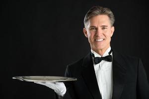 Porträt des selbstbewussten Kellners im Smoking mit Serviertablett foto