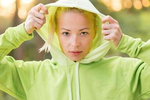 selbstbewusste sportliche Frau, die modischen grünen Kapuzenpulli trägt.