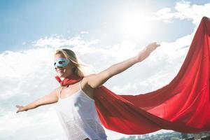 blonder Superheld, der über blauem Himmel und ausgestreckten Armen steht foto