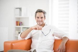 attraktiver Mann, der auf einer Couch lächelt foto