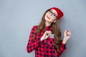 lächelnde Frau, die Musik in Kopfhörern hört foto
