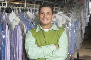 Mann steht vor Kleiderstange foto