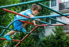 kleiner Junge, der auf Klettergerüst ohne Seil und Helm klettert foto