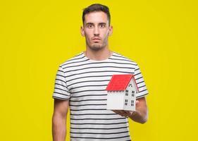 hübscher Immobilienmakler, der ein Haus mit einem selbstbewussten Ausdruck auf klugem Gesicht hält, das ernst denkt