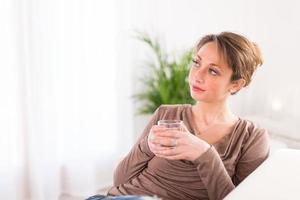fröhliche junge Frauen, die Mineralwasser trinken foto