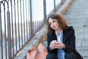 schöne junge Frau, die in einer Treppe außerhalb sitzt foto