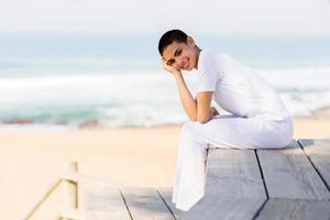 glückliche junge Frau, die am Strand sitzt foto