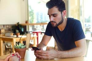 moderner junger Mann mit Handy im Café. foto