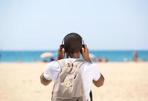 junger Mann mit Kopfhörern und Tasche, die am Strand stehen foto