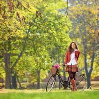 schöne junge Frau, die im Park mit ihrem Fahrrad aufwirft