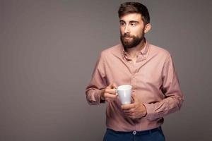 hübscher junger Mann mit Tasse Kaffee.