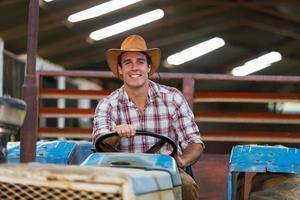 junger Bauer fährt Traktor foto