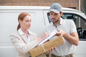 Zustellfahrer, der das Paket außerhalb des Lieferwagens an den Kunden übergibt foto