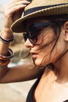 junges Sommermädchen, das einen Hut und eine Sonnenbrille trägt