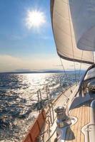 Yacht segelt in Richtung Sonnenuntergang auf blauem Meer