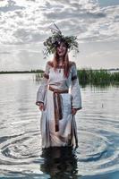 schöne Frau mit Blumenkranz steht im Wasser