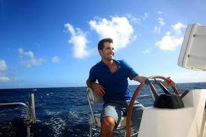 Mann, der sein Segelboot auf Ozean steuert foto