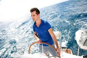 Mann, der ein Segelboot mit Sorgfalt steuert foto