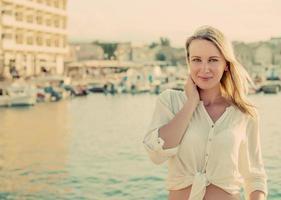hübsche Frau, die gegen Hafen mit Yachten steht. foto