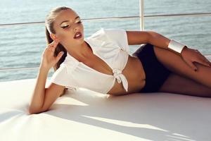 schönes sinnliches Mädchen mit dunklem Haar, das auf Yacht aufwirft