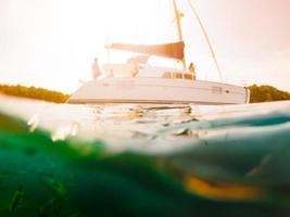 Halbunterwasser-Unschärfeszene der tropischen Insel, der Yacht, des Riffs mit foto