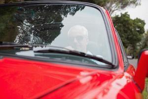 gutaussehender Mann, der rotes Cabrio fährt foto