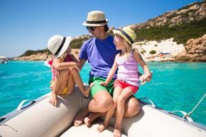 junger Vater mit entzückenden Mädchen, die auf einem großen Boot ruhen foto