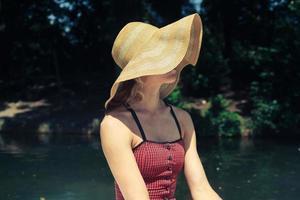 junge Frau, die einen Hut in einem Boot trägt foto