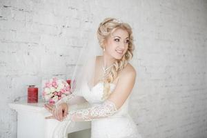 schöne Braut mit Hochzeitsstrauß, der nahe Kamin steht foto