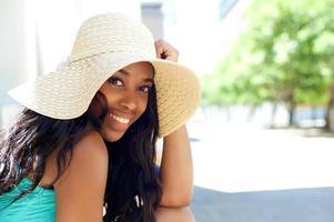 glückliche junge schwarze Frau, die mit Sonnenhut draußen lächelt