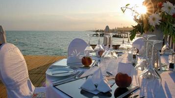 romantische Tischdekoration am Pier bei Sonnenuntergang