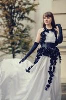 schöne junge Frau im weißen Kleid mit schwarzen Rosen