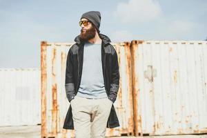 stilvoller Mann, der vor Frachtcontainern aufwirft foto