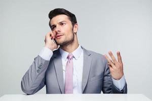 nachdenklicher Geschäftsmann, der am Telefon spricht foto
