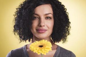 hübsches Mädchen, das lächelt und eine Blüte in ihrer Hand hält.