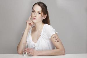 Frauen mit Anker Tattoo und Tasse Wasser foto