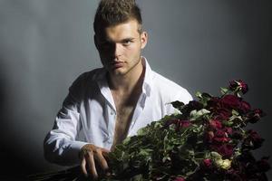 Porträt des schönen Mannes mit Blumen im Studio