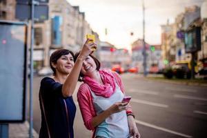 Mädchen, die Telefone benutzen, während sie durch die Stadt gehen.