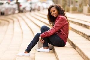 afrikanische Frau draußen sitzen auf Stufen foto