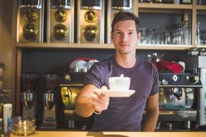 Barkeeper bietet Kaffee an