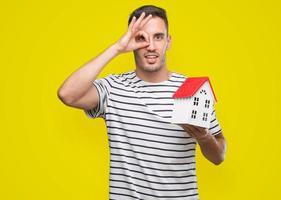 gutaussehender Immobilienmakler, der ein Haus mit dem glücklichen Gesicht hält, das lächelnd tut, ok Zeichen mit Hand auf Auge schauend durch Finger