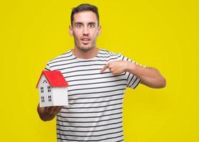 hübscher Immobilienmakler hält ein Haus mit Überraschungsgesicht und zeigt mit dem Finger auf sich