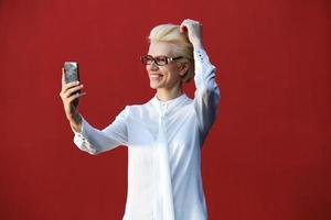 lächelnde junge blonde Frau, die selfie nimmt foto