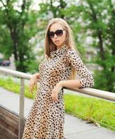 schöne blonde Frau, die ein Leopardenkleid und eine Sonnenbrille in trägt foto